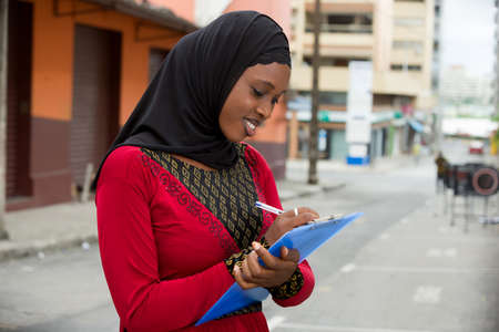 young muslim student girl standing outdoors taking notes smiling.