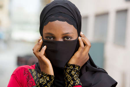 muslim girl standing outdoors with veiled mouth.