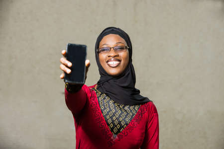 young muslim woman standing in eyeglasses shows mobile phone door laughing.