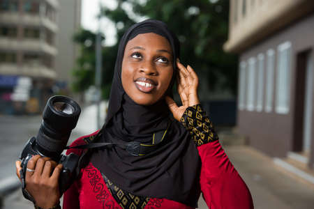 young muslim woman standing outdoors with a camera thinking about looking up there.
