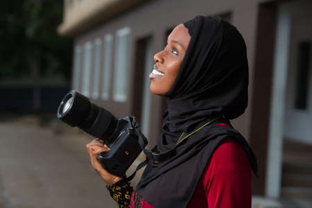 young muslim woman standing outdoors with camera looking up there.