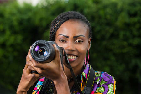 young woman standing in full with camera and looking in front of her smiling.