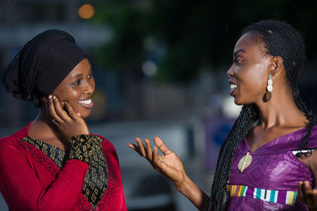 young african women standing outdoors talking to each other while smiling. Stockfoto