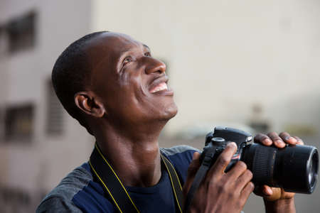 young man standing outdoors with camera staring up at smiling.