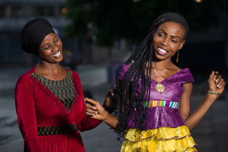 young african woman standing outdoors contemplating the braids of her girlfriend smiling.