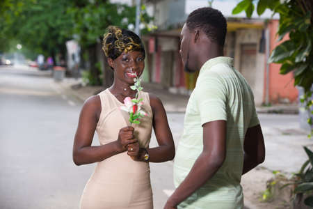 romantic offer to get married. A man makes a surprise to his girlfriend in the city. Valentine's day proposal concept. Young man giving a flower for girlfriend on Valentine's Day.