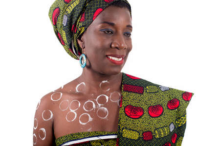 Portrait of a smiling african young woman in african cloth with drawing tinted body. she is wearing a fabric on the shoulder isolated on a white background