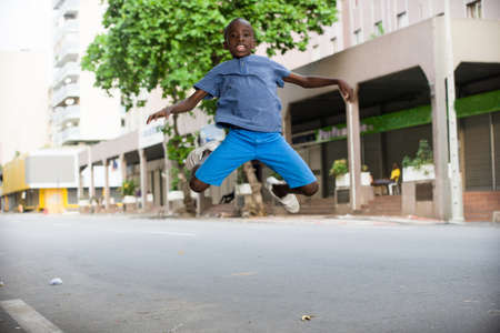 happy smiling child jumping for joy outdoor in the summer in the city street Banque d'images