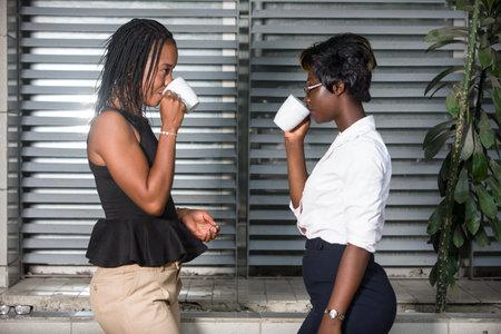 two businesswomen drinking coffee outdoors. Work Balance Concept