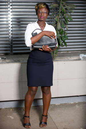 Successful business woman portrait standing near contemporary office building holding a purse against her chest. Happy businesswoman posing outdoors. Pretty woman looking at the camera