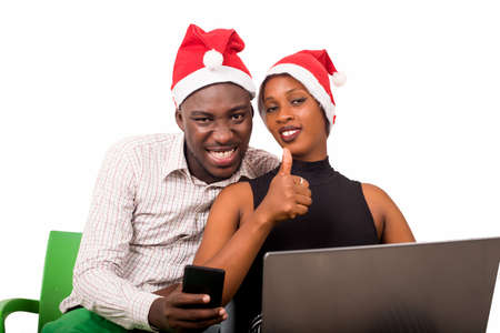 Happy lovers with hands sign having fun, surfing the Internet wearing Christmas hats - Holidays and shopping concept