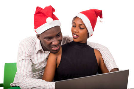 Happy lovers surfing the Internet wearing Christmas hats - Holidays and shopping concept
