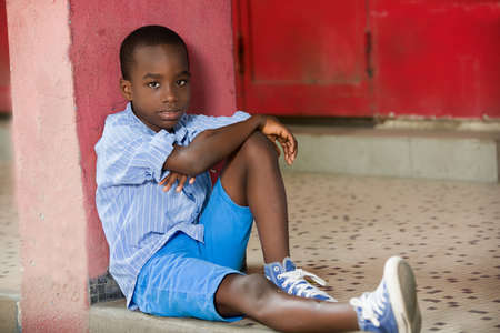 Happy boy sitting alone on the outside against a wall painted in red.Concept shy child, player, alone Stock fotó