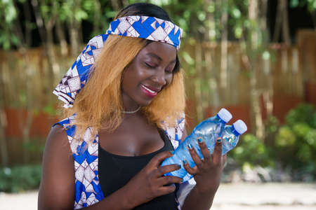 happy woman standing outside holding two bottles of drinking water to drink on the outside hot