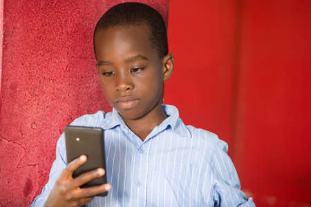 young boy standing in shirt in a studio looking at mobile phone. 免版税图像