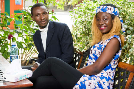 a young african couple sitting in a park watching the camera smiling.