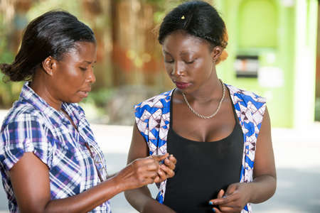 young african woman standing in a shirt explaining something to her girlfriend. 免版税图像