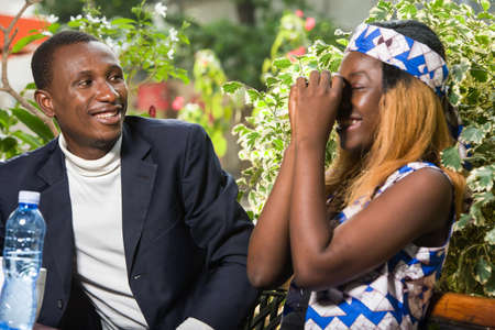 young man sitting in a park watching his laughing girlfriend.