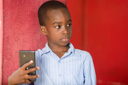 young boy standing in shirt in a studio looking in profile with mobile phone in hand.