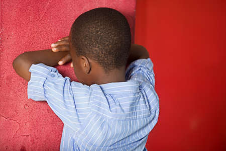 Horizontal shot of an offended child, diverted from camera, stands with his back, face against wall ,. A bad-tempered male boy has a difficult character.