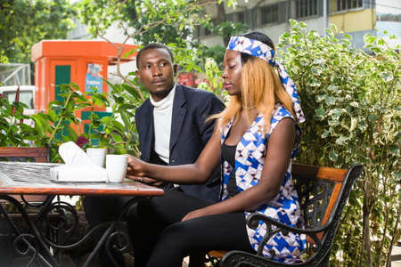 young african couple sitting in a park ready to share tea.