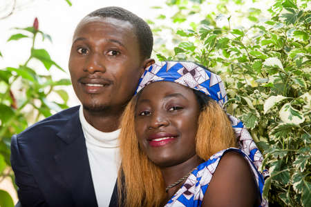 young african couple sitting in an embracing park looking at the camera smiling.