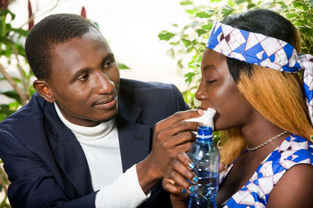 A happy couple in love, a man and a woman eat and drink water for drinking. Romantic rendezvous in a restaurant, man wipes his lover's mouth with a white handkerchief