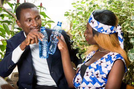 new business team man and woman sitting in office lobby during the day discussing new business ideas. Young man and woman drinking water drinking happy during a meeting.