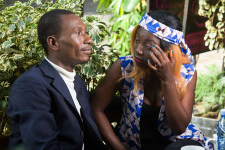 young african couple sitting in a park looking at each other smiling.