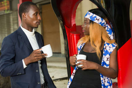 Man and businesswoman drinking coffee while discussing together while holding cups of white coffee outdoors in front of a red and black cafe stall in daylight.