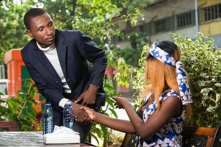 young woman sitting in park shaking hands with her boyfriend.