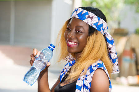 young woman standing outdoors with a bottle of water smiling looking at the camera.