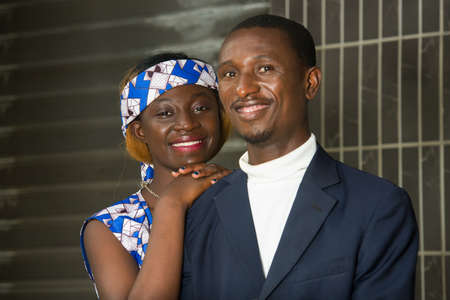 young couple standing near a wall looking at camera smiling.