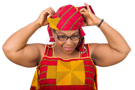 Close-up stylish smiling african mature woman in red african loincloth and glasses standing in studio and arranging her traditional headscarf on her head