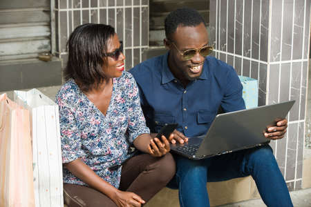 young couple sitting in sunglasses cheering looking at laptop smiling.