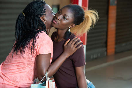 young girl saying goodbye to her girlfriend after their shopping by kissing her on the cheek.