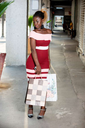 happy portrait of young woman in a red dress walking in the city holding shopping bags
