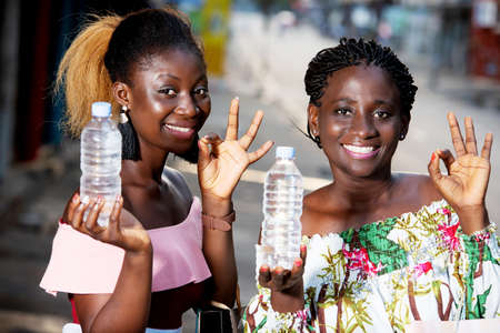 Portrait of two happy girls, drinking and presenting water from a plastic bottle to the camera while having a hand gesture