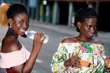 two young women with shopping bags drink mineral water after shopping in the city. concept reduce stress by buying.