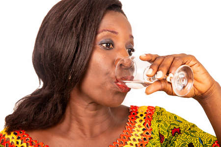 beautiful African adult woman wearing a green loincloth with long black hair, is drinking mineral water in a glass on a white background. health and beauty concept