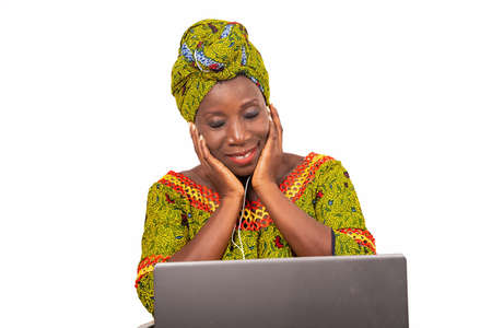 beautiful african adult woman dressed in loincloth and green scarf, enjoys listening to music with headphones, in her laptop while smiling with her eyes closed.