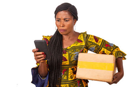 beautiful adult woman is pissed off looking at cellphone while holding a cardboard while smiling