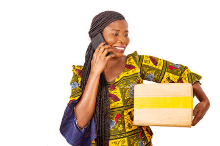 beautiful adult businesswoman talking on the mobile phone holding a cardboard while smiling