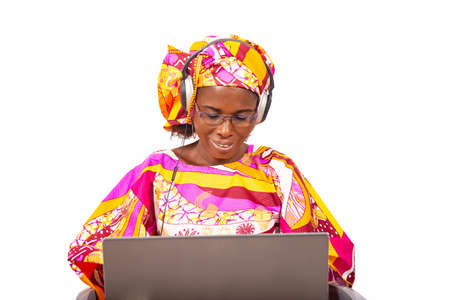 Beautiful adult woman wearing headphones and smiling using video call chat on a laptop while smiling