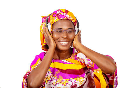adorable woman listening to music in headphones, keeps hands on headphones, holds her eyes open in her glasses, and smiling