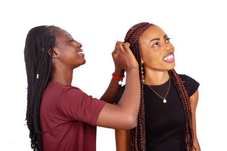 beautiful african girl wearing a red burgundy t-shirt touching the braided hair of her sister dressed in black dress. smiling isolated hard white background Banco de Imagens