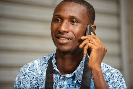 handsome young african photographer sitting outside holding a mobile phone and looking at camera smiling Stock fotó