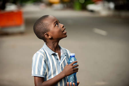 happy little African boy standing sideways holding a plastic bottle and looking up