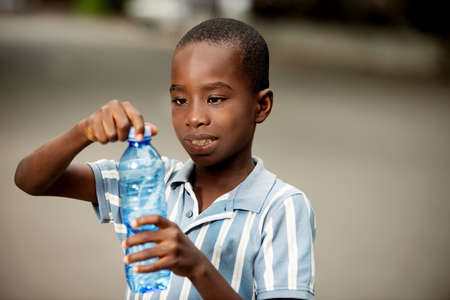 happy little african boy standing and holding a plastic water bottle smiling Stock fotó