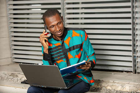 Businessman holding a folder and having a mobile phone conversation with the customer, sitting with a laptop outside the office.